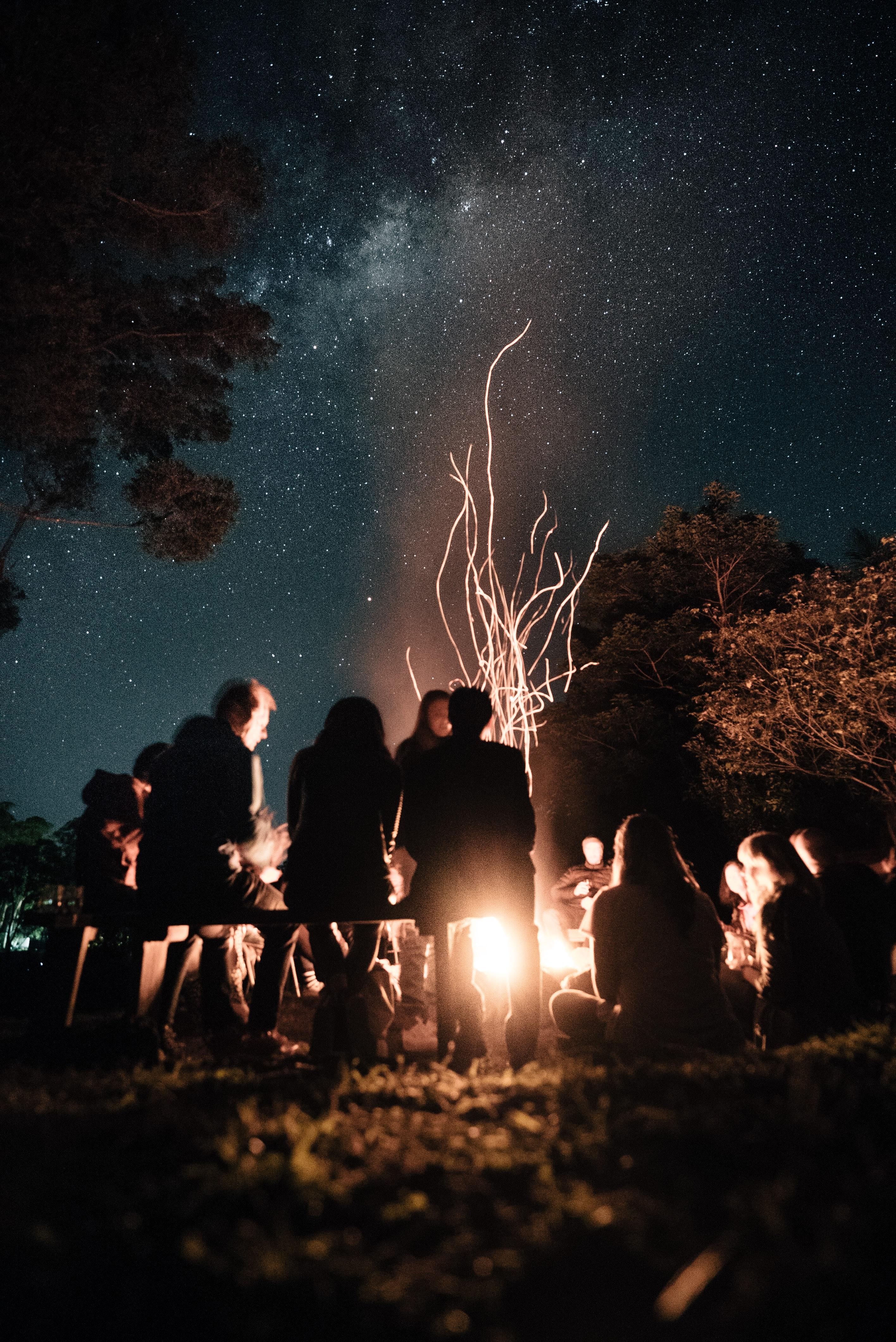 Menschen sitzen zusammen am Lagerfeuer
